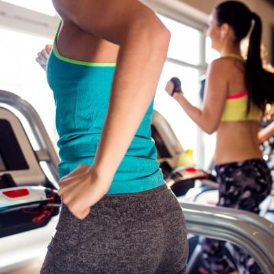 Two attractive fit women running in sports clothes on treadmills in modern gym, sunny day