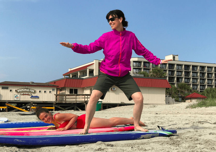 "Practicing ""hanging ten"" during surf lessons in Myrtle Beach - Wellness Vacation"