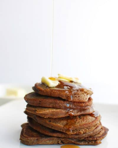 Stack of green banana flour pancakes with syrup being drizzled on top