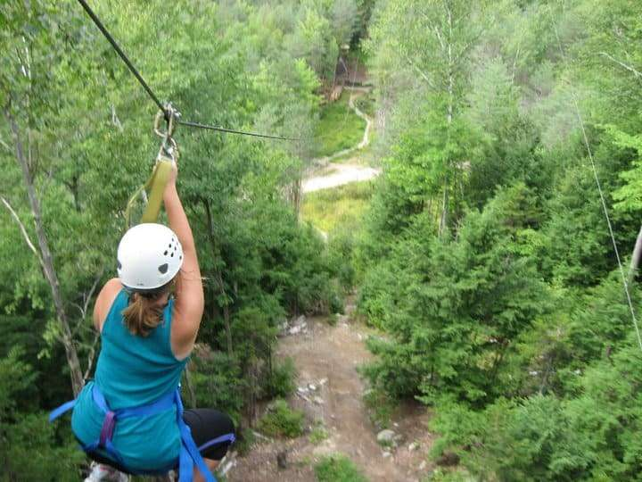 A young woman ziplining in New Hampshire