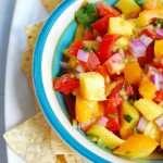 A bowl of mango habanero salsa next to tortilla chips