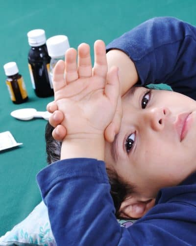Sick child with medics and pills behind him