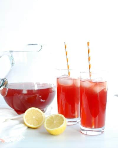 A pitcher and two glasses with sparkling pomegranate lemonade