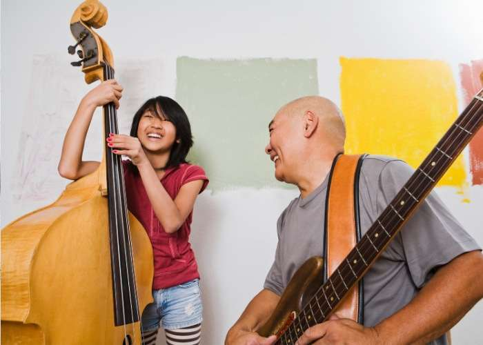 girl playing base with adult playing guitar