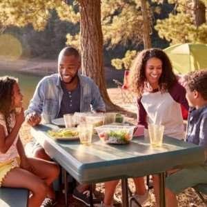 Family camping eating at table